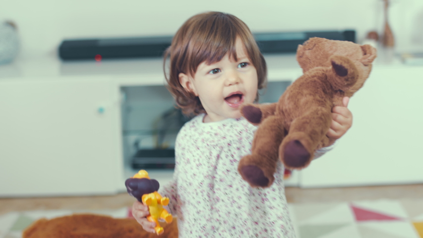 Portrait of cute little one year old girl laughing happily while playing and hugging with her mother at home with a teddy bear. Shot in 6k, cine lens. Instagram style.