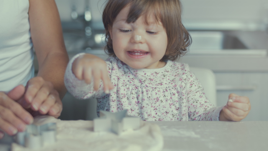 Closeup of young mother and little cute daughter cooking together preparing cookies and pizza with biscuit cutter and a dough in the kitchen. Close up on hands. Shot in 6k, cine lens. Instagram style.