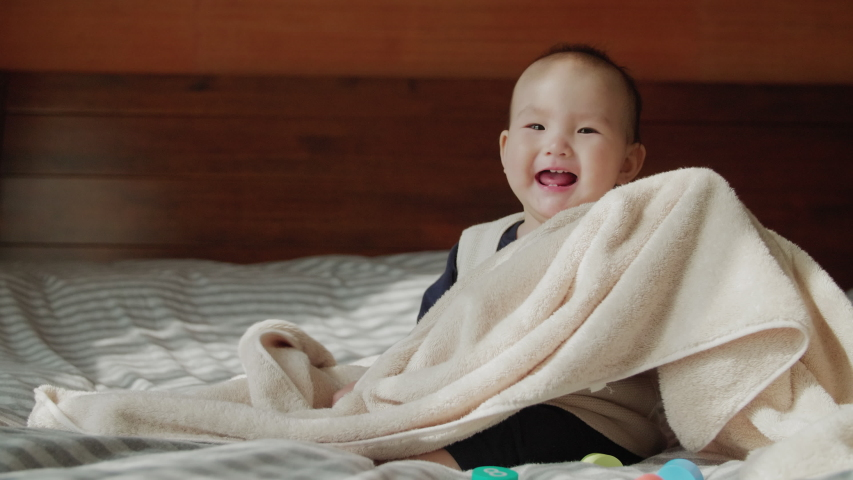 Slow motion of lovely asian baby girl show up from towel blanket adorable Chinese kid playing game hide-and-seek cute 9 months old baby smile sitting in bed