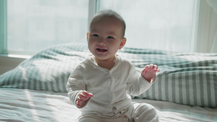 Slow motion of lovely asian baby playing at home in bedroom looking at camera smile 9 months happy baby playing Lovely baby girl crawling in bed Chinese baby girl portrait
