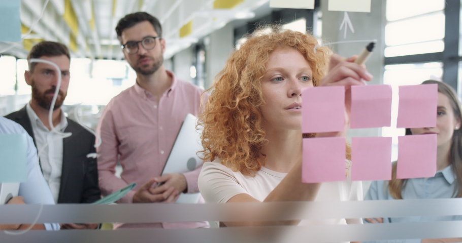 Close up of female office worker using glass board and proposing her problem solving to workmates. Diverse coworkers having corporate meeting and standing near glass wall with sticky notes.