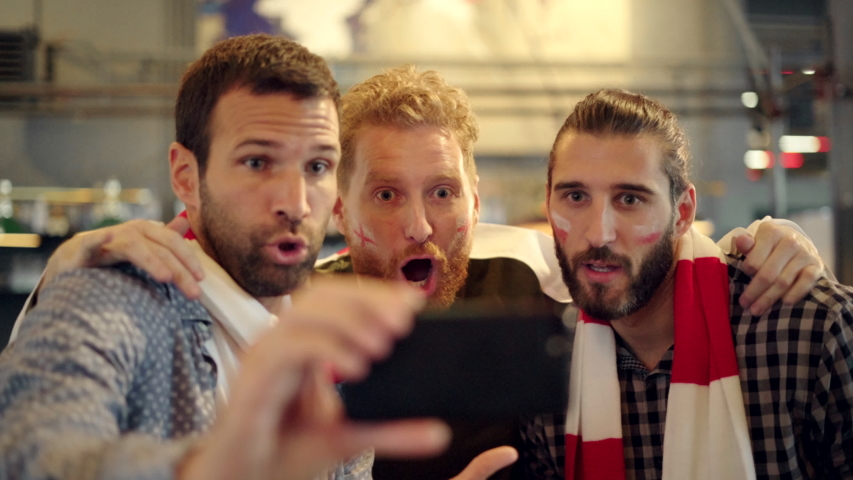 Excited men watching football in streaming on smartphone in bar. Football fans watching game on smart phone and celebrating victory score at pub. Happy supporters cheering and exulting after winning. Royalty-Free Stock Footage #1044263395