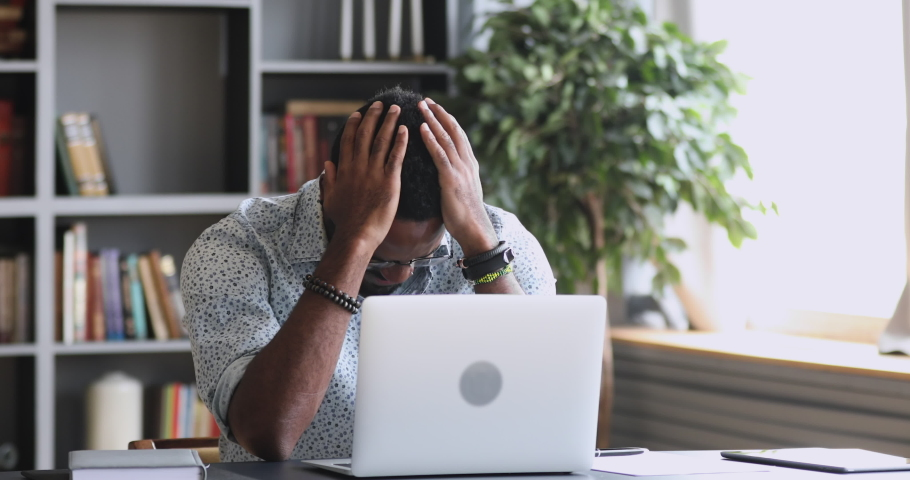 Shocked frustrated african mixed race business man student feel stressed look at computer screen worried of problem read bad online news receive failed exam results concept sit at home office table | Shutterstock HD Video #1044264613