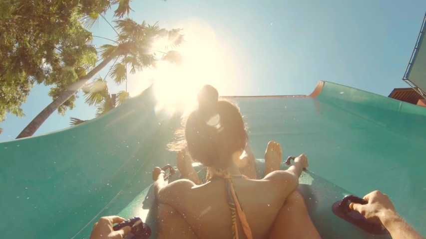 Young Multi Race Couple Having Fun Sliding Down in a Water Slide. Waterpark Summer Travel Activity Concept. First View POV. 4K Gopro Footage. Bali, Indonesia.