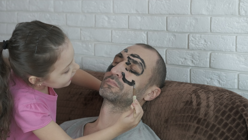 Makeup for dad. The child draws on the face of a sleeping father. | Shutterstock HD Video #1044272773