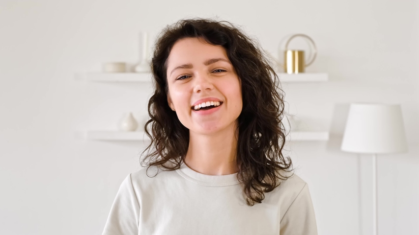 Portrait of a young woman looking at the camera and smiling. Millinale girl with curly hair in a light interior. White shining teeth and smile concept.