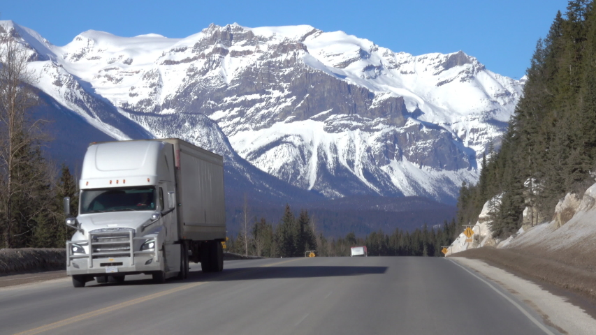Three trucks haul cargo down the highway leading towards the breathtaking snow capped mountains in Jasper National Park. Lorries travel along the famous Icefields Parkway on a sunny winter day.
