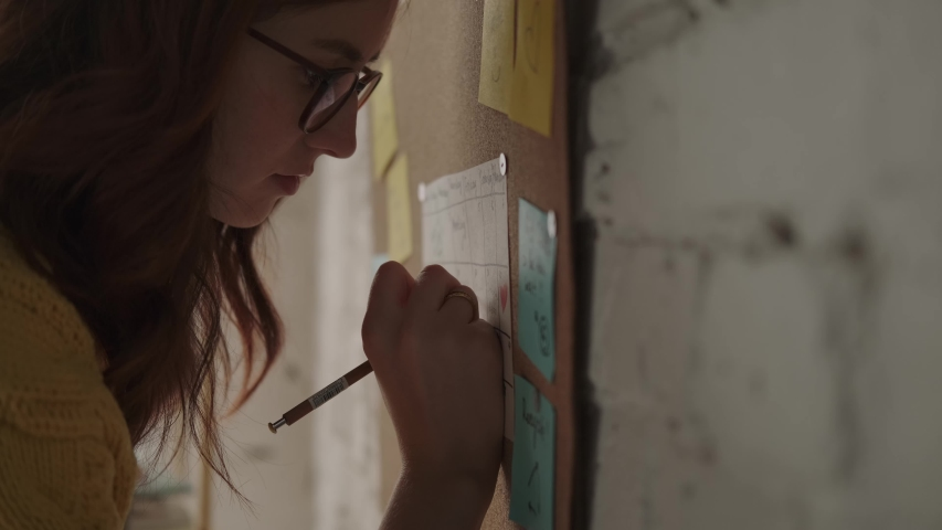 Young modern woman walks up to the wall with a cork board and writes on stickers. Creative woman makes a mental map, design thinking, creative. Prototype development, ideas. | Shutterstock HD Video #1044287770