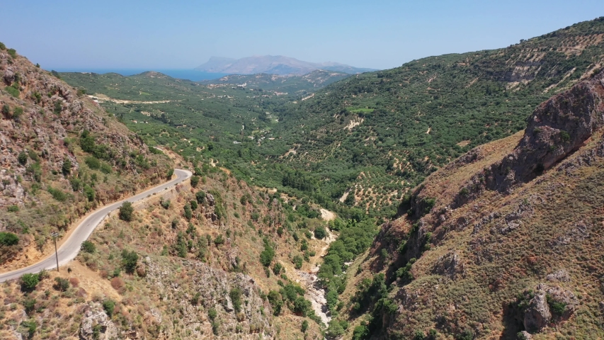 Aerial bird's-eye view video from drone of flight from Topolia Gorge canyon to a mountain valley with olive groves and mountain Topolia village. Kissamos, Chania prefecture, Crete, Greece. | Shutterstock HD Video #1044318301