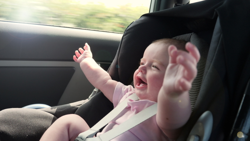 Baby travelling in a Car seat in the back of a vehicle. This child is safely strapped in witha seatbelt on. Slow motion | Shutterstock HD Video #1044319366