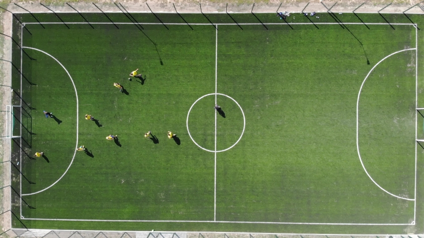 Aerial view of a soccer game being played at nighttime with floodlights lighting the field. | Shutterstock HD Video #1044329224