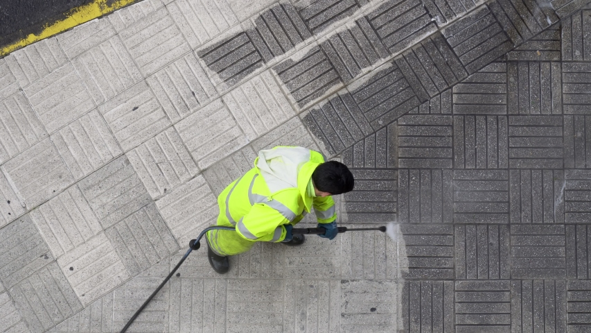 Top view of a Worker cleaning the street sidewalk with high pressure water jet. Public maintenance concept | Shutterstock HD Video #1044333304
