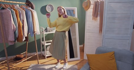 Blonde young Caucasian attractive girl with long hair in skirt and yellow sweater trying on clothes in the cozy big wardrobe and dancing. Indoors.