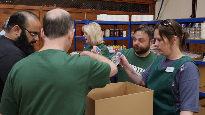 Foodbank volunteers help to sort tinned food and drinks for people in poverty and with social issues