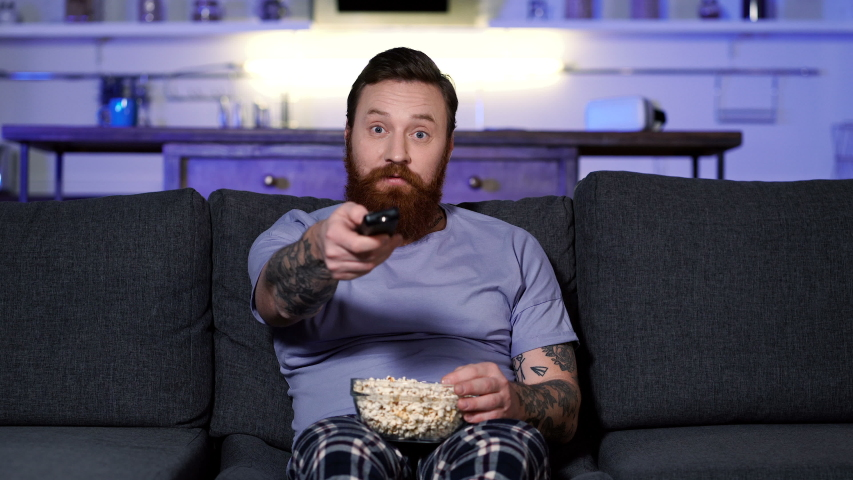 Man watching tv and eating popcorn at home.   Shutterstock HD Video #1044374635