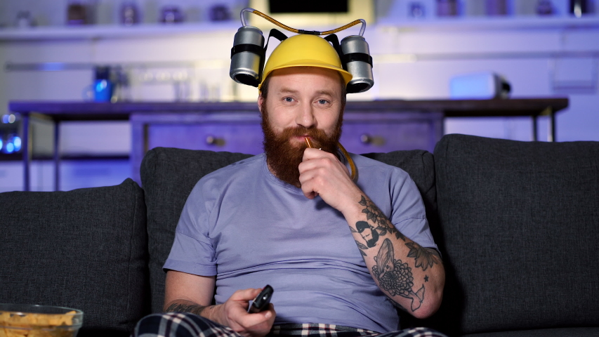 Bearded man with beer helmet sitting on the sofa at home, drinking beer, watching tv and relaxing. | Shutterstock HD Video #1044374641