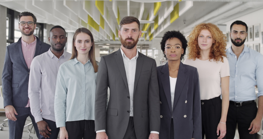Positive multiracial company staff standing and crossing hands in office. Group of successful mixed workers with ther boss looking to camera and smiling. Concept of team portrait. | Shutterstock HD Video #1044377251