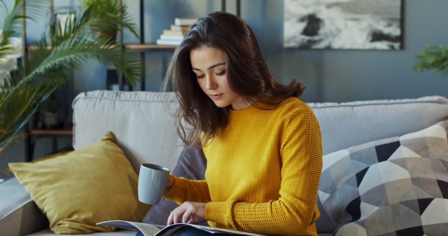 Young pretty Caucasian woman flipping pages and reading a fashion magazine while sipping hot drink and resting on the cozy sofa at home. Pandemic, epidemic, protection, coronavirus, quarantine  Royalty-Free Stock Footage #1044382957