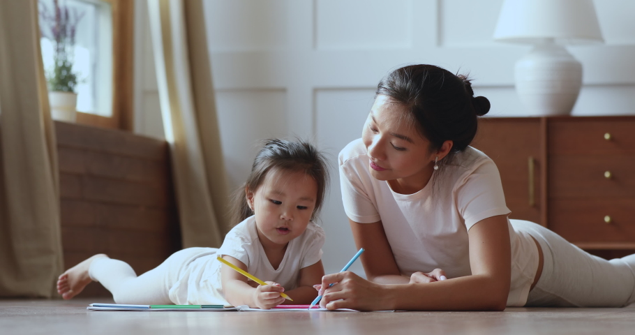 Cute adorable asian ethnic kid girl holding color pencil learn drawing lying on warm floor with young vietnamese mom daycare babysitter talking playing teaching helping little child daughter at home