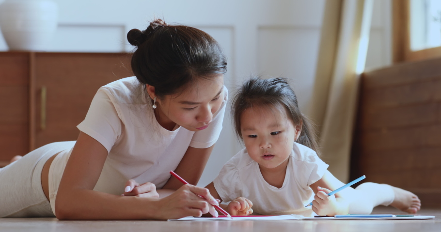 Caring young asian ethnic mum or nanny helping cute kid daughter teaching toddler child daughter drawing picture with pencils lying on warm heated floor in bedroom learn creative art activity at home