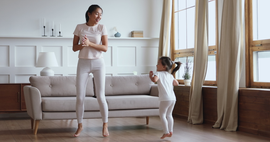 Carefree healthy fit young adult asian mom and child daughter having fun dancing together, happy vietnamese family mother play jump with cute little kid girl enjoy leisure lifestyle activity at home