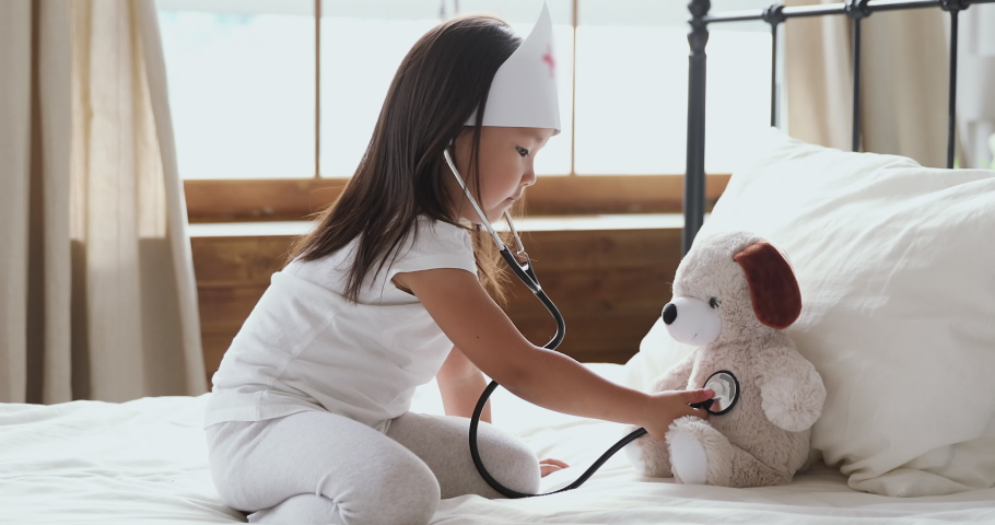 Cute little asian child girl wear medical hat playing game as vet doctor holding stethoscope listening sick dog in bed, adorable preschool korean child pretending doctor treat toy patient in bedroom