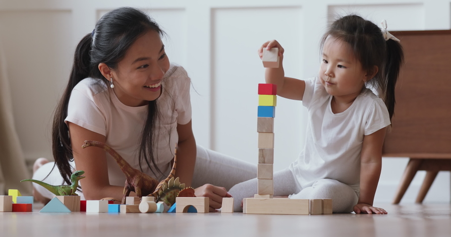 Happy vietnamese family asian mum daycare babysitter playing with focused cute small kid daughter help building castle of wooden blocks having fun talking laughing lying on warm floor in living room