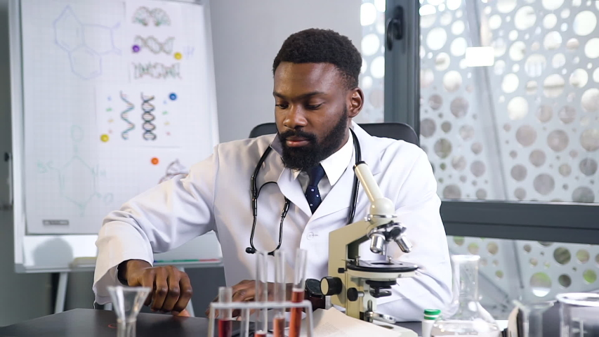 Front view of concentrated high-skilled bearded dark-skinned doctor in white uniform looking into microscope and planning to write down the result on the laptop | Shutterstock HD Video #1044393337