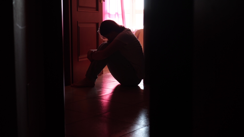 Silhouette of a young girl sitting on the floor in the dark room, depression, pain. Domestic violence, family problems, Stress, violence, The concept of depression and suicide.
