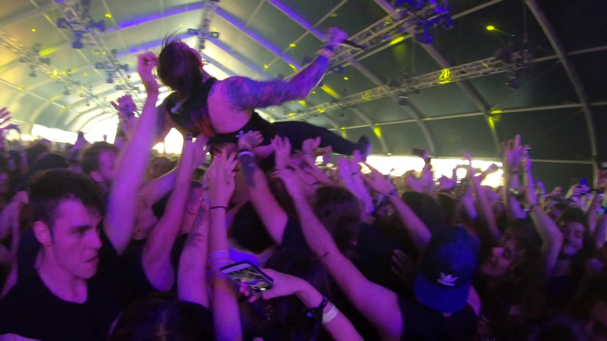 BONTIDA, ROMANIA – JULY 20, 2019: Vocalist of metalcore band  While She Sleeps performing a crowd surfing and stage diving during a live concert at Electric Castle festival