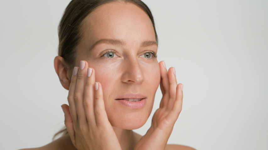 Close-up beauty portrait of young woman with smooth healthy skin, she gently touches her face with her fingers on white background and smiles | Shutterstock HD Video #1044399334
