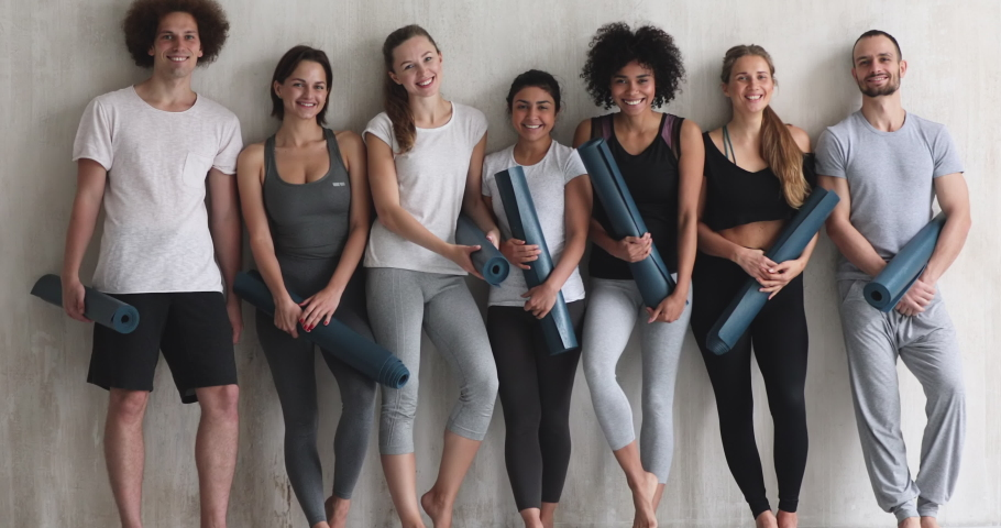 Multi-ethnic girls and guys leaned on wall smiling pose for camera, before or after work out people in sportswear holds yoga mats looking happy and healthy, well-being, hobby, sports lifestyle concept Royalty-Free Stock Footage #1044404395