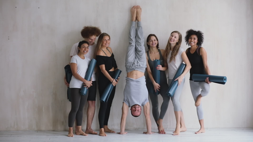 Seven multi-ethic girls guys holding mats standing near wall smiling posing looking at camera, caucasian male performs handstand people having fun waiting yoga class or resting after work out indoors Royalty-Free Stock Footage #1044404407