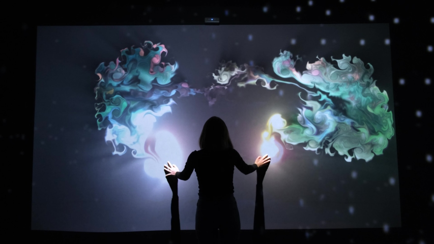 Girl plays with interactive video installation, hands draw the shape heart. New art form, generative graphics. Silhouette of girl draws multi-colored paints interactive installation. Royalty-Free Stock Footage #1044426391