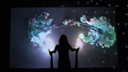 Girl plays with interactive video installation, hands draw the shape heart. New art form, generative graphics. Silhouette of girl draws multi-colored paints interactive installation.