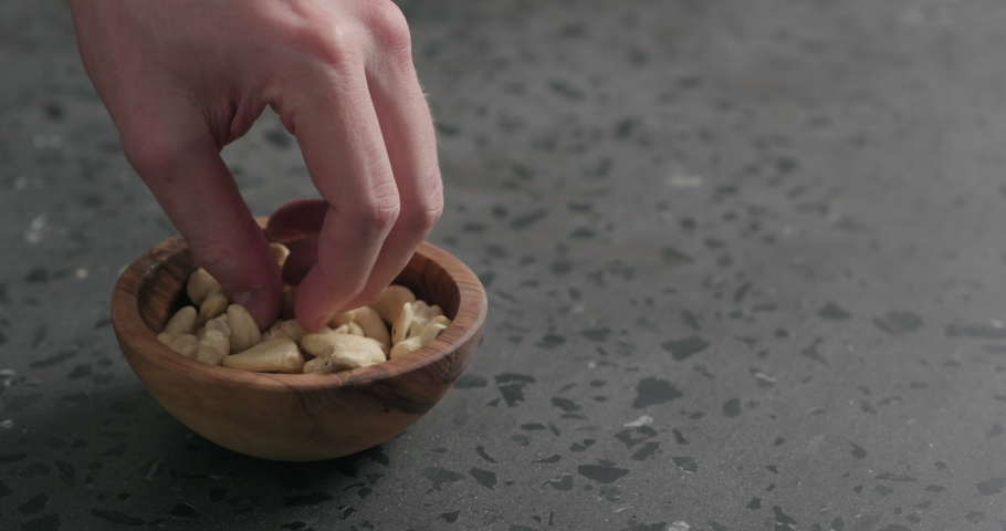 Slow motion man hand takes cashew nuts from olive bowl on countertop