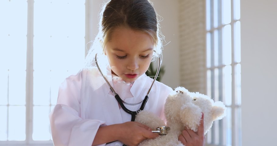 Cute adorable little preschool kid girl wear white medical uniform holding stethoscope listening sick toy teddy bear patient, smart small child playing hospital game as doctor pretend nurse concept