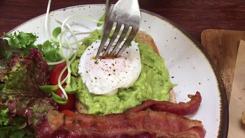 Cutting perfect poached eggs with avocado paste on toast ,crispy fried bacon ,fresh green salad that calls Open Faced Avocado Spread Sandwiches recipe in restaurant as healthy breakfast ,bunch menu | Shutterstock HD Video #1044454144