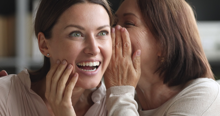 Funny two generation women family friends share secrets gossip having fun together, older mature mother whisper news rumors in ear of excited young adult daughter laugh bonding at home, closeup view | Shutterstock HD Video #1044454840