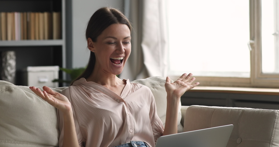 Excited female user customer sit on sofa using laptop computer get amazing sale offer winning online bid, overjoyed beautiful woman using notebook feel ecstatic reading great online news at home