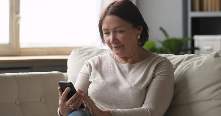 Smiling senior lady using smartphone texting message sit on couch, middle aged woman grandma hold phone typing sms enjoying communication in mobile app at home, older people and modern tech concept Royalty-Free Stock Footage #1044454930