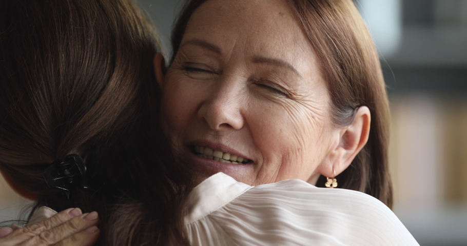 Caring senior mature beautiful mom hugging adult grown young daughter enjoying cuddling embracing with eyes closed, two generations women family reunion and sweet tender mothers love concept, closeup #1044454954