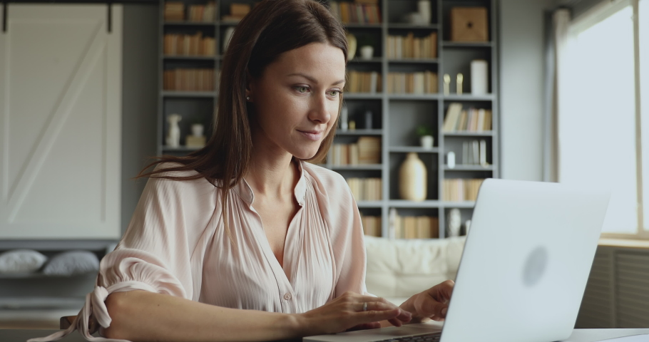 Young adult business woman typing on laptop computer working in internet, beautiful female professional user lady using pc technology doing online job in office or browsing web sit at home table Royalty-Free Stock Footage #1044454966