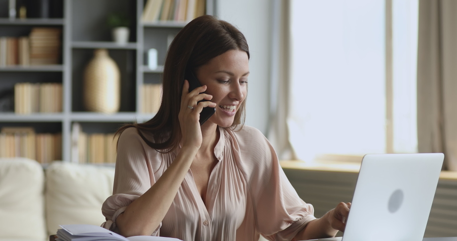 Smiling young business woman professional talking on phone using laptop sit at home office desk, happy female customer make mobile call confirming online website shopping order delivery concept