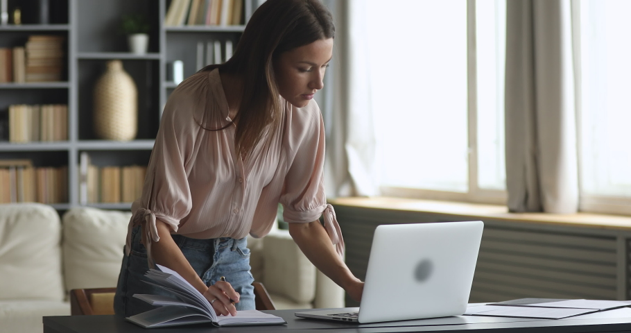 Young female entrepreneur using laptop writing notes stand at home office desk, adult 30s business woman professional work on computer planning agenda with personal planner and online calendar Royalty-Free Stock Footage #1044454981