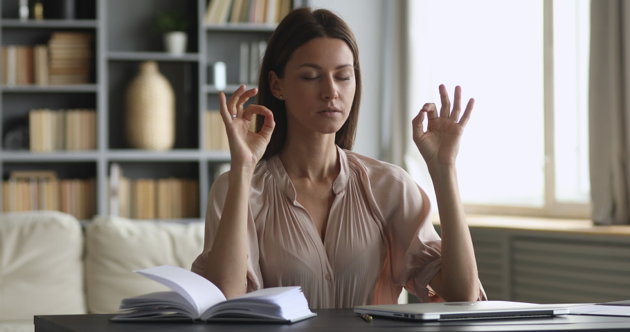 Mindful calm beautiful business woman sit at work desk do yoga exercise take break relax eyes closed at home office, young female worker meditate at workplace feel zen no stress peace of mind concept | Shutterstock HD Video #1044454984