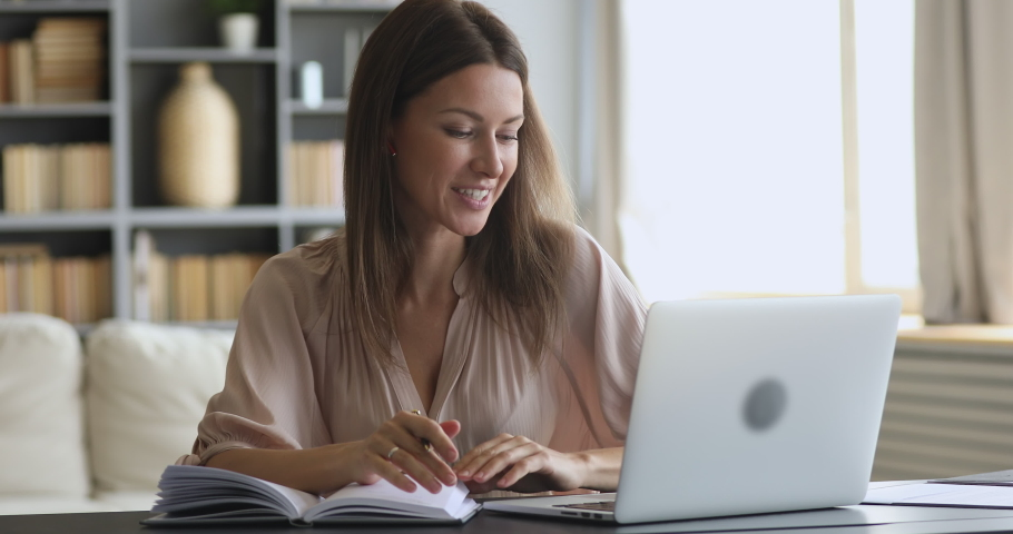 Smiling female online tutor counselor english teacher wear wireless earphone speaking teaching web class doing conference video call chat on laptop make notes communicate by webcam at home office Royalty-Free Stock Footage #1044455011