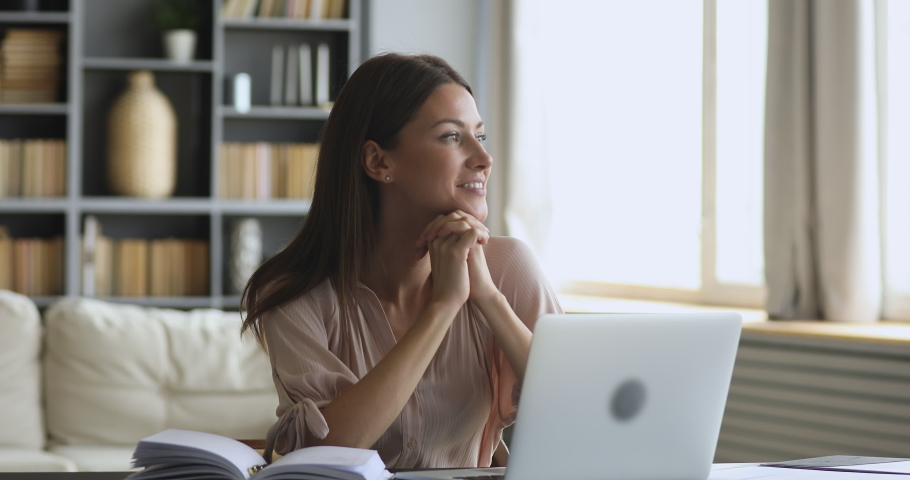 Thoughtful smiling young woman writer professional take break from work looking away dreaming thinking or future opportunities search new creative ideas sit at home office table with laptop computer | Shutterstock HD Video #1044455014