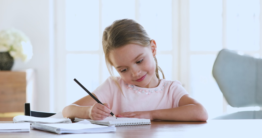 Cute smart primary school child girl learning writing doing math homework sit at home table, adorable pretty little preschool kid studying alone making notes, children elementary education concept | Shutterstock HD Video #1044455035
