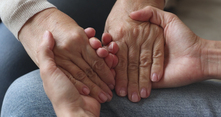 Young woman hold old female hands giving support concept, kind adult daughter caregiver helping senior mature mother grandparent patient, elder people respect, comfort and care concept, close up view